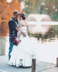 biker wedding photo of bride and groom with pond and fountain in background